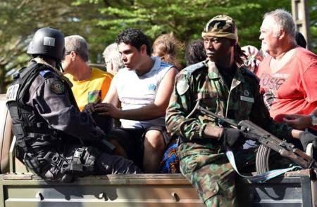 Pasukan bersenjata Pantai Gading mengevakuasi dan melindungi warga pengunjung Beach Resort Grand Bassam, setelah serangan bersenjata pada hari Minggu 13 Maret 2016, sore. - AFP/Getty Images